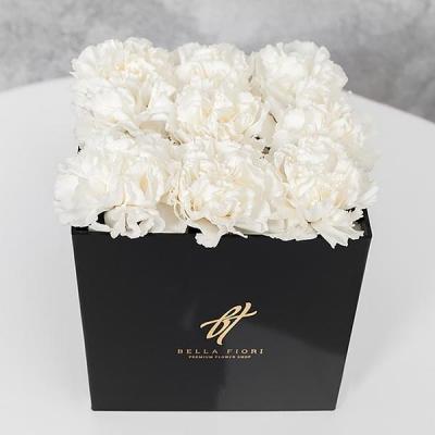 Белые гвоздики в черной коробке
